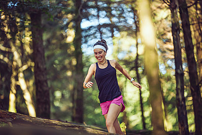 Smiling sportswoman running in forest - p300m2282415 by Mikel Taboada