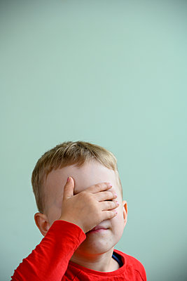 Blonde boy hiding face with hand - p427m2206487 by Ralf Mohr