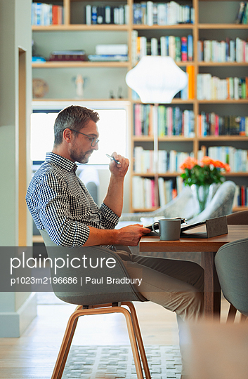 Businessman using digital tablet, working from home - p1023m2196686 by Paul Bradbury