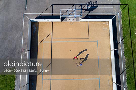 Young women playing basketball, aerial view - p300m2004513 von Stefan Schurr