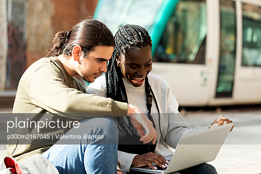 Happy young couple using laptop at tram stop in the city - p300m2167045 by Valentina Barreto