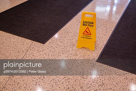 Zeichen, Nasser Fußboden in einem Bürogebäude - p397m2013392 von Peter Glass