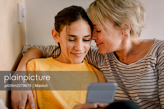 Happy mother embracing daughter using mobile phone in bedroom - p426m2279675 by Maskot