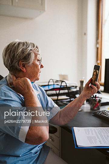 Senior female doctor consulting patient through video call at medical clinic - p426m2279735 by Maskot