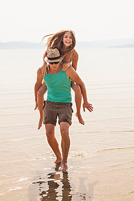 Croatia, Young couple on beach fooling about - p1026m762667f by Dario Secen