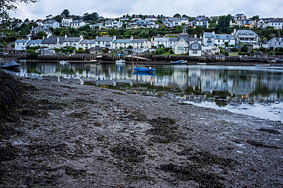 A small sheltered harbour and mooring for boats. Houses on the hillside overlooking the bay, and lights at dusk.  - p1100m1522321 by Mint Images