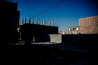 Person walks past housing development at twilight - p1118m2151096 by Tarik Yaici