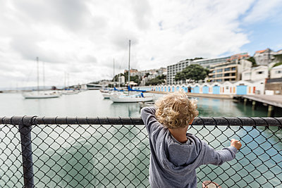 Toddler boy looking over fence by the ocean - p1166m2124347 by Cavan Images