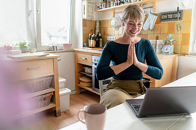 Portrait of laughing woman with laptop practicing yoga in the kitchen - p300m2140867 by Kniel Synnatzschke