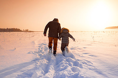 Mari father and son walking in snowy field - p555m1414021 by Aliyev Alexei Sergeevich