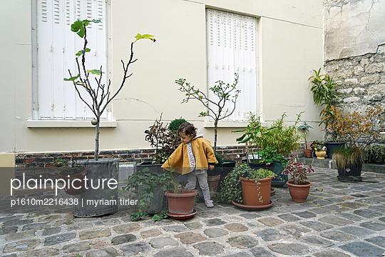 a child among flower pot - p1610m2216438 by myriam tirler