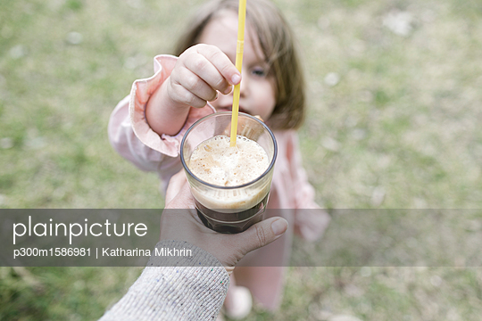 Little girl putting straw in glass of coffee - p300m1586981 von Katharina Mikhrin