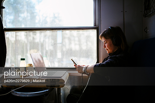 Female professional text messaging through smart phone while traveling in train - p426m2279829 by Maskot