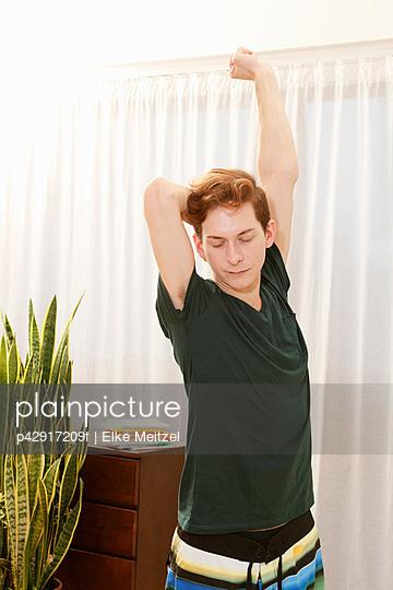 Man stretching in bedroom - p42917209f by Elke Meitzel