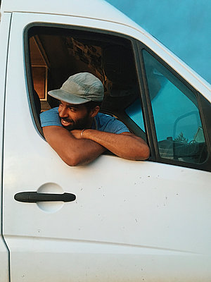 Low angle view of man looking through window while sitting in motor home - p1166m2011679 by Cavan Images