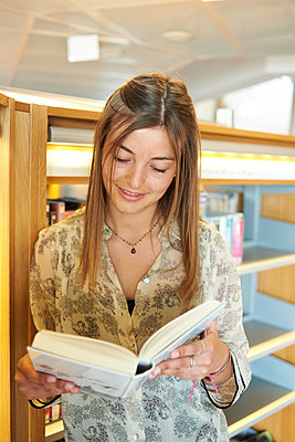 Portrait of smiling young woman with  book at the library - p300m2029344 by Ivan Gener