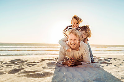 Father having fun with his son on the beach, lying in the sand on top of each other - p300m2167069 by Floco Images