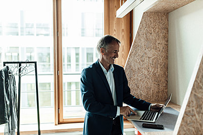 Smiling businessman using laptop while standing at lobby in office - p300m2266283 by Gustafsson