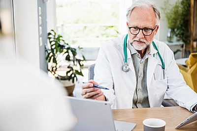 Mature male doctor looking at laptop while holding pen at desk - p300m2294155 by Uwe Umstätter