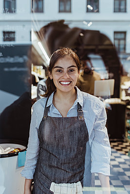 Portrait of smiling female owner at deli store - p426m2270589 by Maskot
