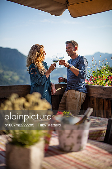 Young couple takes a glass of wine on the terrace - p1007m2222285 by Tilby Vattard