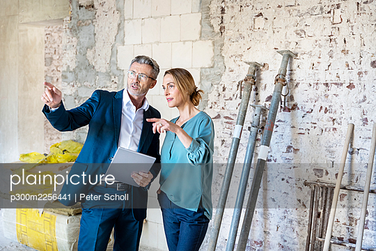 Male expertise holding digital tablet while standing by colleague at construction site - p300m2256441 by Peter Scholl