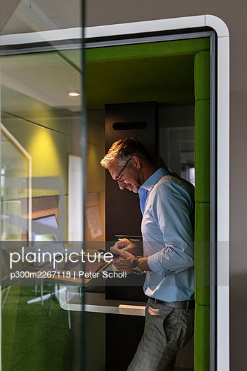 Mature businessman using mobile phone while standing in soundproof cabin at office - p300m2267118 by Peter Scholl
