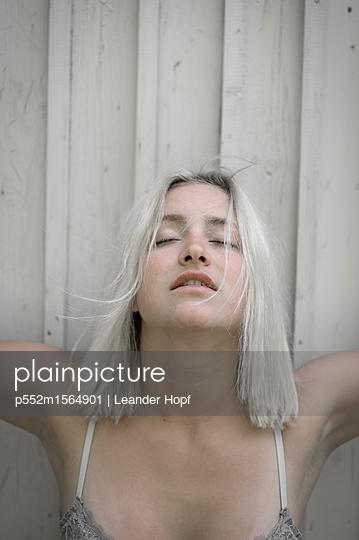 Junge Frau mit platinblonder Frisur in sexy Pose - p552m1564901 von Leander Hopf