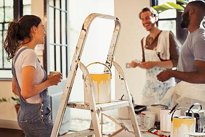 Friends drinking coffee and painting living room - p1023m1519991 by Paul Bradbury