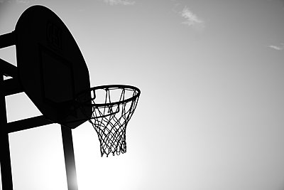 Outdoors basketball backboard against the sky, in black and white - p1423m2210722 by JUAN MOYANO
