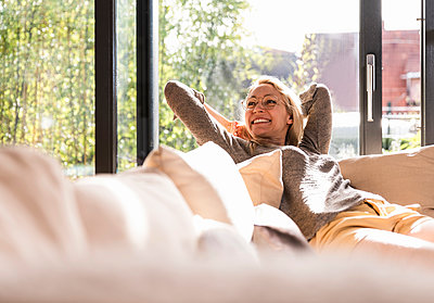 Happy mature woman relaxing on the couch at home - p300m1587752 by Uwe Umstätter