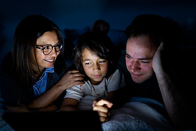 Parents and son lying together on bed at home using digital tablet - p300m2189534 by Valentina Barreto