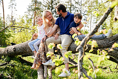 Family sitting on fallen tree in forest - p300m2197490 by Stefanie Aumiller