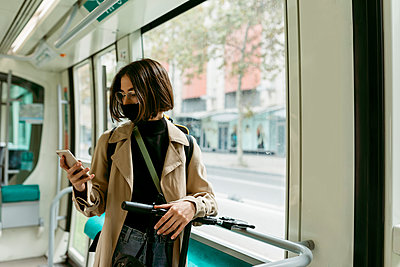 Woman with electric push scooter and face mask using mobile phone while standing in tram - p300m2227346 by Valentina Barreto