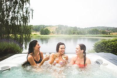 Cheerful female friends enjoying wine in hot tub against lake during weekend getaway - p426m2035954 by Maskot