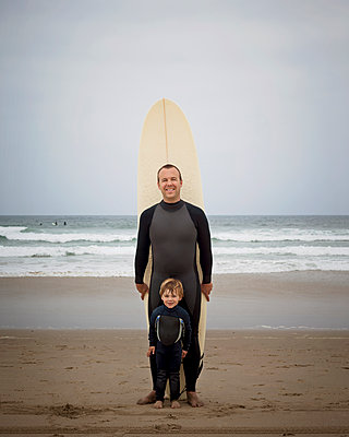 Caucasian father and son in wetsuits with surfboard - p555m1479236 by Pacific Images