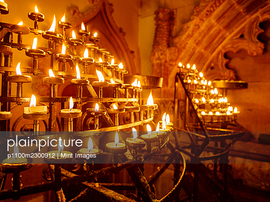 Lit candles in racks in a historic church - p1100m2300912 by Mint Images