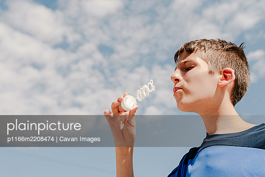 Young white boy blowing a soap bubble outdoors with sky at background - p1166m2208474 by Cavan Images