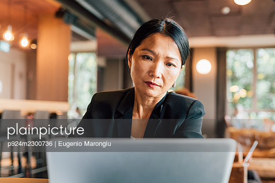 Italy, Businesswoman using laptop at table in creative studio - p924m2300736 by Eugenio Marongiu