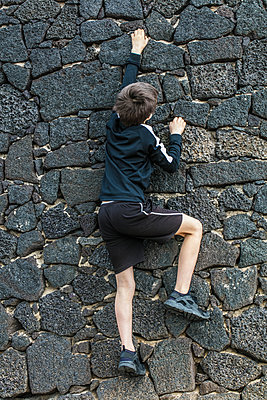 Junge klettert eine Steinmauer hinauf - p1082m1538967 von Daniel Allan