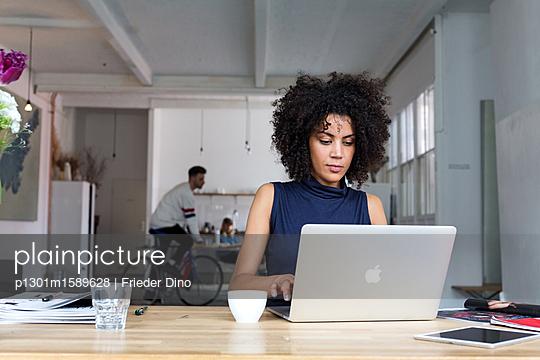 Attraktive Geschäftsfrau am Laptop in einem modernen Büro - p1301m1589628 von Delia Baum
