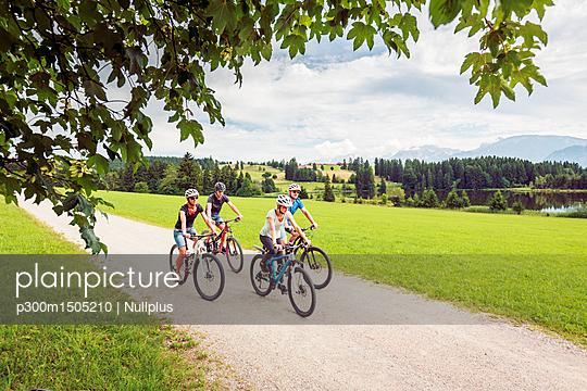 Germany, Bavaria, Pfronten, family riding mountain bikes at ladeside - p300m1505210 by Nullplus