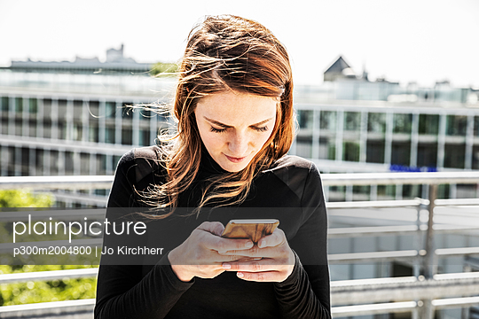 Woman text messaging on roof terrace - p300m2004800 von Jo Kirchherr