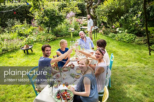 Freunde auf Gartenparty stoßen mit Weißwein an  - p788m1165322 von Lisa Krechting