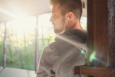 Profile young male runner listening to music with headphones - p1023m2161295 by Agnieszka Olek