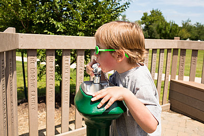 Boy drinking water from fountain at park - p1166m1403958 by Cavan Images