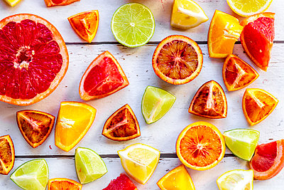 Sliced citrus fruits on white wood - p300m2083818 by Sandra Roesch