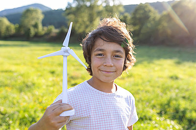 Boy smiling while holding wind turbine toy in meadow - p300m2221736 by Valentina Barreto