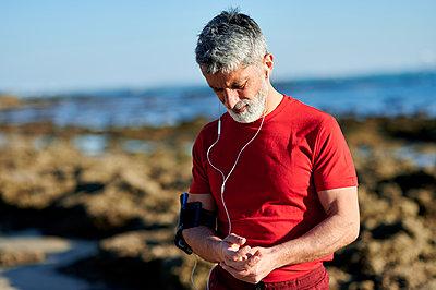 Mature man touching hands while standing at beach - p300m2275729 by Kiko Jimenez