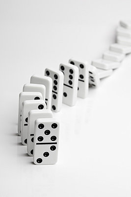 Dominoes falling over in a chain reaction - p301m714344f by Larry Washburn